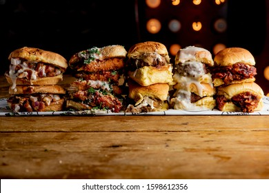 Sliders. Bacon cheeseburgers. Variety of beef hamburger sliders. Traditional classical American diner or bar food menu item favorite. Variety of beef sliders.