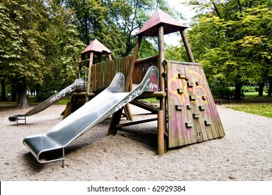 Slides in park during autumn, wide range of colors, green trees and yellow sand, wooden playground