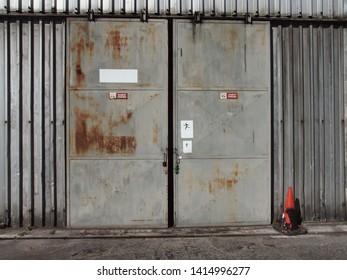 The sliding metal door of an small old airport hangar.