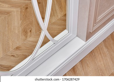 Sliding mirror wardrobe doors with overlays decor. White sliding mirror wardrobe on parquet background. Close-up