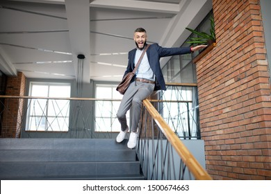 Sliding on banister. Cheerful bearded dark-haired man having fun while sliding on the banister