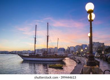 Sliema bay waterfront with sailboat at sunset - Malta