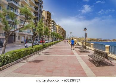 SLIEMA, MALTA - 28 MAY 2016: Walking across the seafront of Sliema a visitor can admire the riviera bay of Sliema and Saint Julians in Malta island.