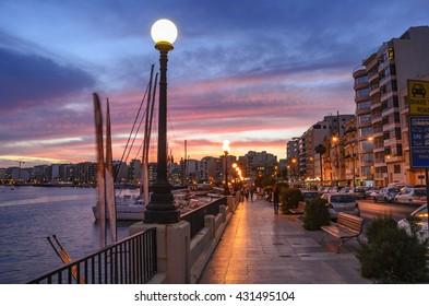 SLIEMA, MALTA - 30 MAY 2016: Walking across the seafront of Sliema a visitor can admire the riviera bay of Sliema and Saint Julians in Malta island.
