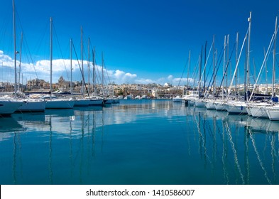 Sliema, Malta; April 11, 2019: Rows of yachts in the Sliema marina on a sunny day with blue sky and picturesque clouds