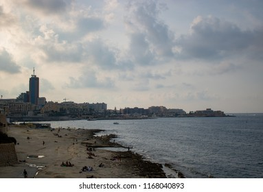 SLIEMA, MALTA - AUGUST 05, 2018: view from Sliema of the sea with people on the shore in a cloudy day.