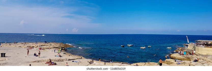 SLIEMA, MALTA - AUGUST 05, 2018: panoramic view of a beach in Sliema, Malta. People having fun and relax on a sunny day.