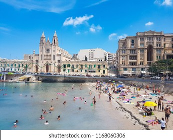 SLIEMA, MALTA - AUGUST 05, 2018: church of our lady of mount carmel and a beach in Sliema, Malta. People relaxing and having fun on the beach in a summer day.