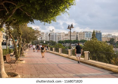 SLIEMA, MALTA - AUGUST 05, 2018: people stroll along the seafront in Sliema, Malta in a summer day.