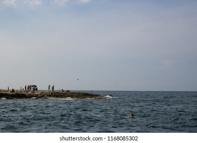 SLIEMA, MALTA - AUGUST 05, 2018: rocky beach in Sliema with people relaxing on a summer day.