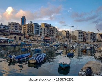 SLIEMA, MALTA - AUGUST 05, 2018: a port with many small boats and buildings on a summer day in Sliema, Malta.