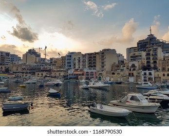 SLIEMA, MALTA - AUGUST 05, 2018: a port with many small boats and buildings at sunset in Sliema, Malta.