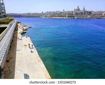 Sliema, Malta - Jul 6 2018: Sliema beach in Malta, with rocky coastline and Valleta's downtown visible in the background