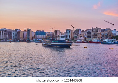 SLIEMA, MALTA - JUNE 18, 2018: The modern coast of Sliema, facing Valletta Northern Harbour, with ships and boats along the shore, on June 18 in Sliema.