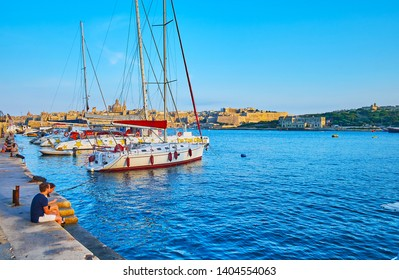 SLIEMA, MALTA - JUNE 19, 2018: The line of sail yachts, moored in Northern Harbour with a view on medieval Valletta and Manoel Island on background, on June 19 in Sliema