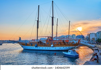 SLIEMA, MALTA - JUNE 19, 2018: Watch the sunset over the harbor, surrounded by modern residential and tourist neighborhoods, the ships and yachts are bobbing on the purple waters, on June 19 in Sliema
