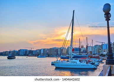 SLIEMA, MALTA - JUNE 19, 2018: The evening walk along the Sliema waterfront with a view on line of modern buildings, sail yachts and the bright sunset sky, on June 19 in Sliema