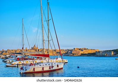 SLIEMA, MALTA - JUNE 19, 2018:  Enjoy the walk along the evening promenade of resort with a view on yachts and ships in Northern Harbour and Valletta on the background, on June 19 in Sliema