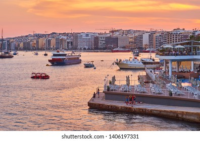 SLIEMA, MALTA - JUNE 19, 2018: The fiery sky over the harbor of Sliema resort with a view on the small beach and modern tourist neighborhood on background, on June 19 in Sliema