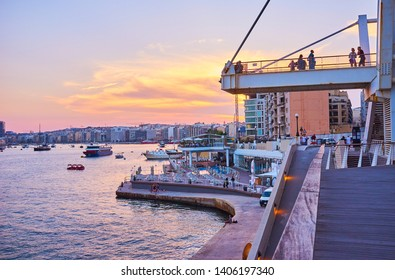 SLIEMA, MALTA - JUNE 19, 2018: The picturesque evening in resort with a view on harbor with ships, fiery sky and comfortable coastal promenade of Tigne Point peninsula, on June 19 in Sliema