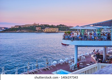SLIEMA, MALTA - JUNE 19, 2018: Crowded open air terrace of the coastal restaurant on Tigne Point peninsula with a view on Valletta Northern Harbor and Manoel Island on twilight, on June 19 in Sliema