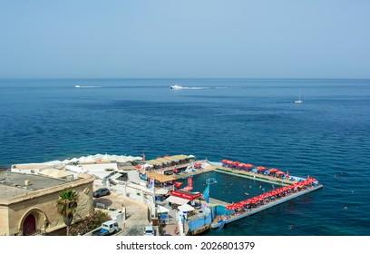 Sliema, Malta - June 26, 2021: Public open-air sea water swimming pool on the Sliema beach near Point Battery, also known asFort Sliema, a popular restaurant nowadays.