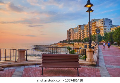 SLIEMA, MALTA - JUNE19, 2018: Morning seaside promenade is nice spot for sport activity, such as jogging or Nordic walking, so locals and tourists often enjoy the sunrise here, on June 19 in Sliema.