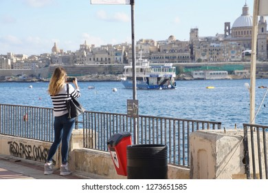 SLIEMA, MALTA - NOV 30, 2018 - Young woman taking picture of ferry and Valletta waterfront from   Sliema, Malta