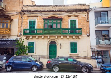 SLIEMA, MALTA - September 2018: Colorful wooden green doors and window frames of the old house in Sliema, Malta