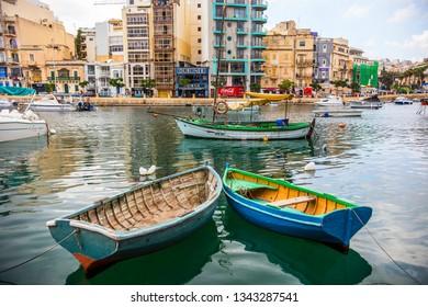 SLIEMA, MALTA - September 2018: Colorful boats on the water in Sliema Bay, cloudy morning in Sliema, Malta
