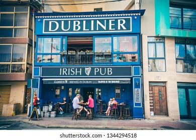 "SLIEMA, MALTA - September 2018: Irish pub ""Dubliner"" with people sitting outside in Sliema, Malta"