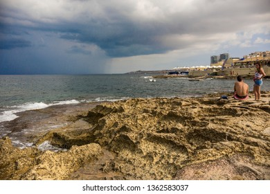 Sliema, Malta - September 2018: People on the beach at Sliema, Malta. Stony Sliema beach
