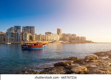 Sliema, Malta - Sunrise with traditional maltese boat and apartments of Tigne point taken from Manoel island on a hot summer day