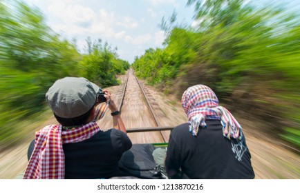 Slight out of focus unidentified tourists on  a high speed bamboo train in Battambang, Cambodia.