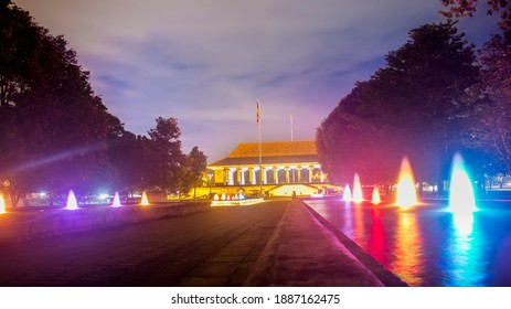 Slightly angled long exposure night view landscape photo of Independence Square building with colorful water fountain lights along the walking path and blue sky in the background. Colombo, Sri Lanka.