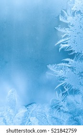 Slightly blurred beautiful frost pattern on a window glass in winter (with copy space for your text), abstract winter background