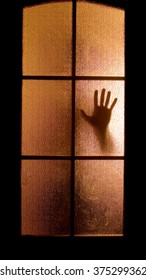 Slightly blurred silhouette of a hand behind a glass door (symbolizing horror or fear)
