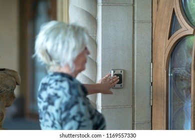 Slightly blurry foreground woman pressing black button on doorway wall for doorbell in front of glass and wooden door
