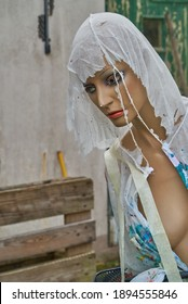 slightly damaged female display dummy with a torn and used disposable painters suit in front of a wall of a vintage house
