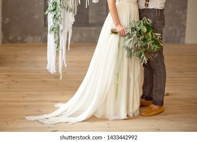 Slightly disheveled fresh and airy bridal bouquet with a grinn ball, brunia, eringum, eustoma, asparagus and eucalyptus in the hands of the bride in a white boho style wedding dress