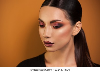 slightly embarrassed by the lowered gaze of the European-Asian girl, the hair is collected orange background the eyes of the lips are painted.