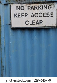 Slightly rusty No Parking Keep Access Clear sign attached to a blue corrugated metal fence / gate