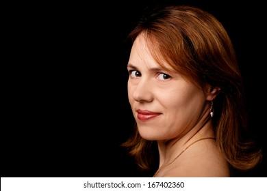 Slightly smiling young Caucasian woman. Closeup studio portrait on black background
