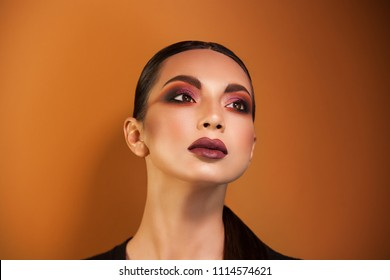 slightly throws back our head, we see a thin, delicate neck, whose gaze is directed into the distance, an unusual makeup accentuates her eyes, lipstick orange image background.