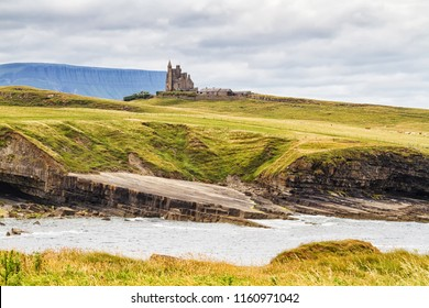 Sligo, Ireland. Famous Classiebawn Castle with Belbulbin mountain at the background in Sligo, Ireland. Cloudy day in summer with green grass and overcast sky
