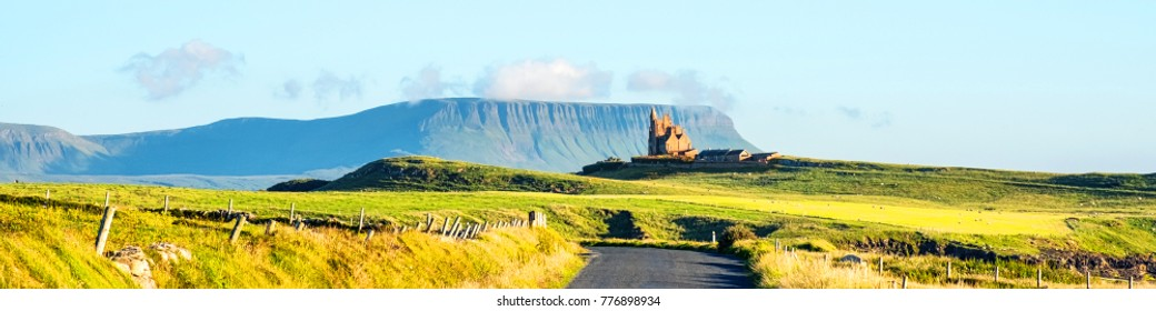Sligo, Ireland. Famous Classiebawn Castle with Belbulbin mountain at the background in Sligo, Ireland. Sunny day in summer with green grass and blue sky