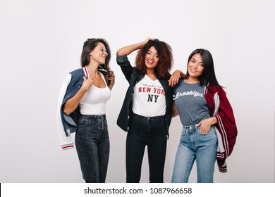 Slim african girl in black pants  spending time with asian and latin friends. Indoor portrait of glad young ladies posing with pleasure on white background.