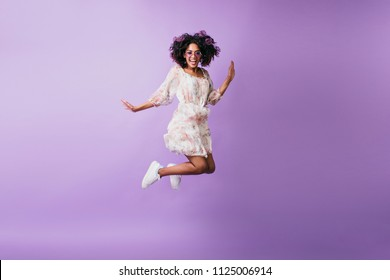 Slim african woman in white sneakers jumping and laughing. Indoor photo of good-humoured black girl dancing on purple background.