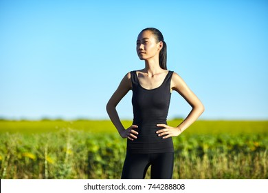 Slim athletic Asian woman resting in field in sunny day. Half body portrait of girl in black sportswear with hands on hips, model looking thoughtfully into the distance and enjoying the sun