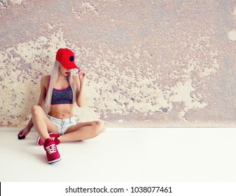 Slim Athletic Blonde Woman in a Red Cap and Red Sneakers Sitting by the Wall